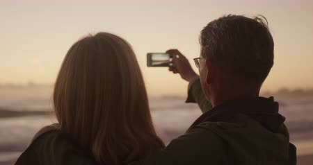 fotografie : Rear view close up of a senior Caucasian couple enjoying time in nature, sitting on the beach during sunset, smiling while taking a selfie with their smartphone in slow motion Filmati Stock