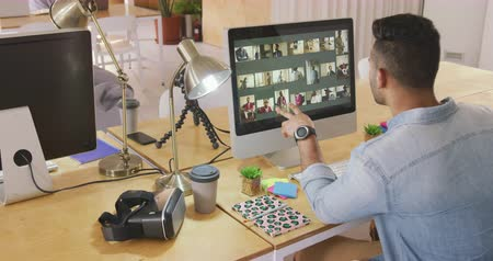 generation z : Rear view of a mixed race man concentrated working in a creative office, looking at computer screen and choosing pictures Stock Footage