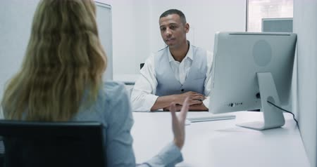 sollicitatiegesprek : Front view of a mixed race man working in an office, talking with a Caucasian blond woman and using computer
