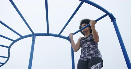 pull out : Low angle front view of mixed race woman enjoying free time on a playground, doing pull ups, in slow motion Stock Footage