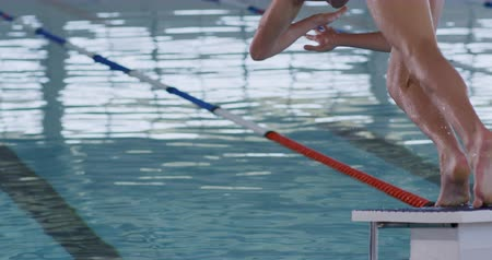 plunging : Rear view of a Caucasian male swimmer at a swimming pool, diving from a starting block into the pool, plunging into the water in slow motion Stock Footage