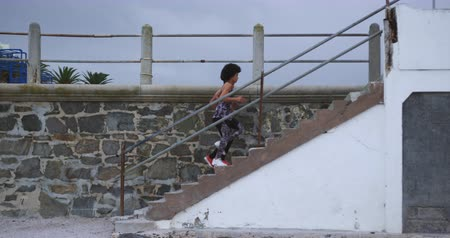 ikrek : Side view of two mixed race women enjoying free time by the seaside, running up the stairs, in slow motion