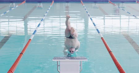 plunging : Rear view of Caucasian male swimmer at a swimming pool, diving from a starting block and plunging into the water, in slow motion