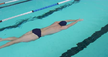 nadador : Side view of Caucasian male swimmer at a swimming pool, swimming under the water in a lane during a swimming competition, in slow motion