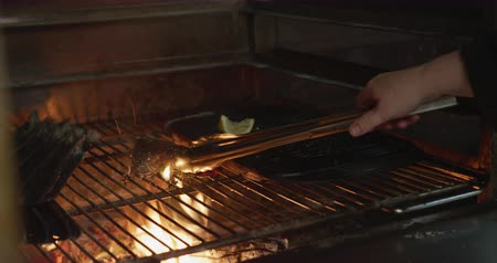 tang : Close up of hands of a Caucasian female cook working in a busy restaurant kitchen, turning meat with tongs inside grill, pouring oil over flames. Busy chefs at work in commercial kitchen.