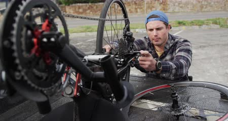 adversidade : Front view of a Caucasian man in a wheelchair assembling parts of a recumbent bicycle in the boot of his car by the sea in slow motion