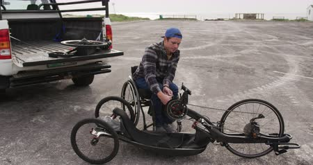 逆境 : Front view of a Caucasian man in a wheelchair assembling parts of a recumbent bicycle in a car park by the sea in slow motion