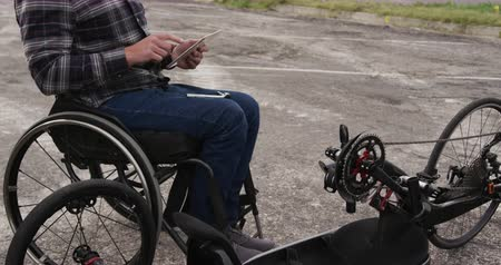 paraplegic : Side view mid section of a Caucasian man in a wheelchair, using a tablet  in a car park by the sea in slow motion Stock Footage
