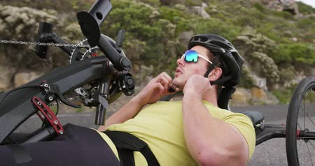 paraplegic : Side view of a fit Caucasian man in sportswear training outdoors, fastening his helmet, on a quiet country road in slow motion