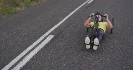 paraplegic : Front view of a fit Caucasian man in sportswear training outdoors, riding a recumbent bicycle, cycling on a quiet country road Stock Footage
