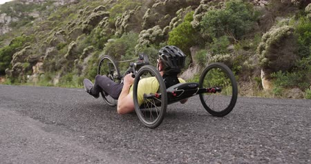 paraplegic : Side view of a fit Caucasian man in sportswear training outdoors, riding a recumbent bicycle, cycling on a quiet country road