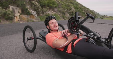 paraplegic : Front view of a fit Caucasian man in sportswear training outdoors, riding a recumbent bicycle on a quiet country road, looking to camera and smiling in slow motion