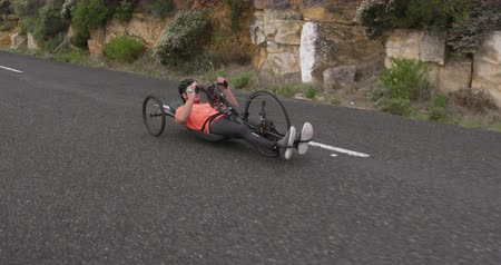 adversidade : Side view of a fit Caucasian man in sportswear training outdoors, riding a recumbent bicycle, cycling on a quiet country road in slow motion Stock Footage
