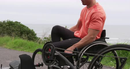 paraplegic : Side view of a fit Caucasian man in sportswear training outdoors, sitting in his wheelchair after riding a recumbent bicycle, the coast in the background, slow motion