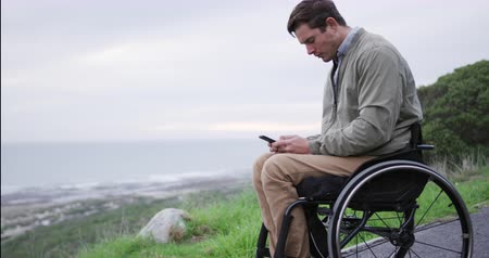 adversidad : Side view of a Caucasian man in a wheelchair, using his smartphone in the countryside by the sea in slow motion Archivo de Video