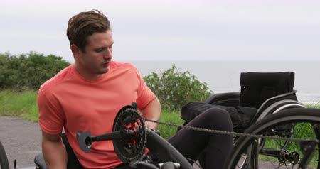paraplegic : Side view of a fit Caucasian man in sportswear training outdoors riding a recumbent bicycle, getting off it after cycling, with his wheelchair waiting to one side, the coast in the background, slow motion