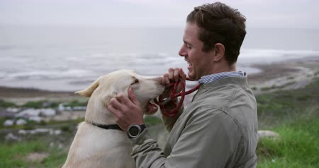 paraplegic : Side view of a Caucasian man in a wheelchair enjoying taking a walk with his dog in the countryside by the sea, playing with his dog in slow motion