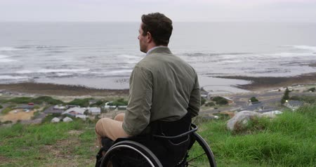 adversidade : Side view of a Caucasian man sitting in a wheelchair relaxing during free time in the countryside, enjoying a view of the coast, in slow motion