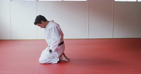a genoux : Side view of a focused mixed race male judo coach wearing white judogi, kneeling on mats in the gym before judo training in slow motion
