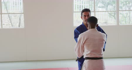free throw : Front view of a mixed race male judo coach and teenage mixed race male judoka, wearing blue and white judogi, practicing judo during a training in a gym, the coach throwing the teenager on the mat in slow motion.