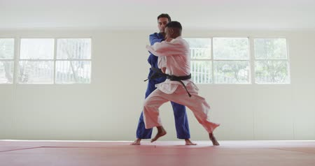 free throw : Front view of a mixed race male judo coach and teenage mixed race male judoka, wearing blue and white judogi, practicing judo during a training in a gym, the teenager throwing the coach on the mat in slow motion.