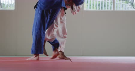 free throw : Rear view low section of a mixed race male judo coach and teenage mixed race male judoka, wearing blue and white judogi, practicing judo during a training in a gym, the teenager throwing the coach on the mat in slow motion. Stock Footage