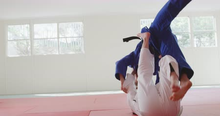 free throw : Rear view of two teenage Caucasian and mixed race female judokas wearing blue and white judogi, practicing judo during a sparring in a gym in slow motion.