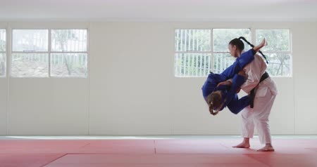 free throw : Side view of two teenage Caucasian and mixed race female judokas wearing blue and white judogi, practicing judo during a sparring in a gym in slow motion.