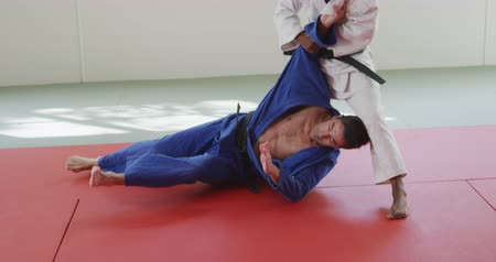 free throw : Front view of a mixed race male judo coach and teenage mixed race male judoka, wearing blue and white judogi, practicing judo during a training in a gym, teenager throwing the coach on the mat in slow motion. Stock Footage