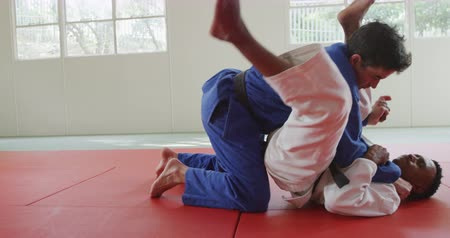 konkurenti : Side view of a mixed race male judo coach and teenage mixed race male judoka, wearing blue and white judogi, practicing judo during a training in a gym, the coach strangling the teenager on the mat in slow motion.