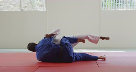 free throw : Side view of a mixed race male judo coach and teenage mixed race male judoka, wearing blue and white judogi, practicing judo during a training in a gym, fighting on the mat together in slow motion. Stock Footage