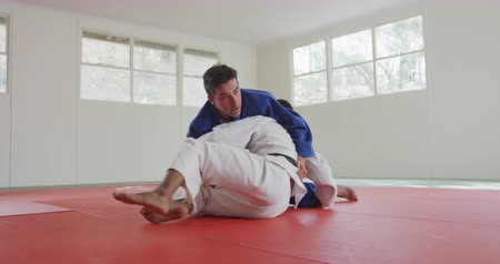 free throw : Front view of a mixed race male judo coach and teenage mixed race male judoka, wearing blue and white judogi, practicing judo during a training in a gym, lying on the mat together in slow motion.
