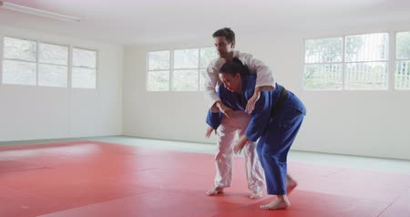 free throw : Side view of a mixed race male judo coach and teenage Caucasian female judoka, wearing blue and white judogi, practicing judo during a training in a gym, the teenager throwing the coach on the mat in slow motion.