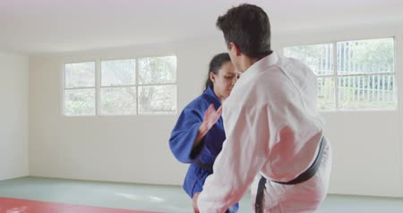 free throw : Rear view of a mixed race male judo coach and teenage Caucasian female judoka, wearing blue and white judogi, practicing judo during a training in a gym, the teenager throwing the coach on the mat in slow motion.