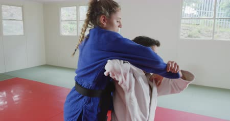 free throw : Side view of a mixed race male judo coach and teenage Caucasian female judoka, wearing blue and white judogi, practicing judo during a training in a gym, the coach throwing the teenager on the mat in slow motion.