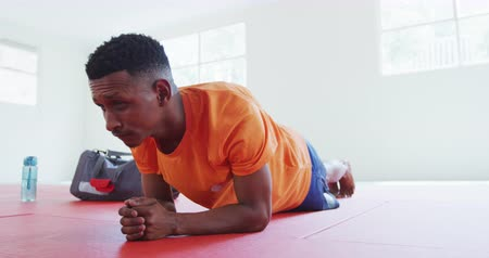 konkurenti : Side view of a mixed race teenage male judoka wearing orange t-shirt in a gym, warming up before the judo training, doing plank on gym mats, with a gym bag in the background in slow motion. Dostupné videozáznamy