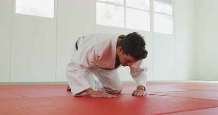 ajoelhado : Low angle side view of a mixed race male judo coach wearing white judogi, kneeling and bowing on mats in the gym before judo training in slow motion.