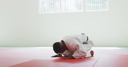 ajoelhado : Side view of a teenage mixed race male judoka wearing white judogi, kneeling and bowing on mats in the gym before judo training in slow motion.