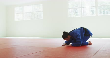 konkurenti : Side view of a teenage mixed race female judoka wearing blue judogi, kneeling and bowing on mats in the gym before judo training in slow motion.