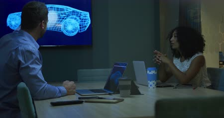 car designer : Side view of a Caucasian businessman and mixed race businesswoman working late in a modern office together, sitting at a table in conference room, television screen displaying a 3d model of a car prototype, discussing brainstorming pointing, laptop comput Stock Footage