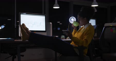 kahve molası : Side view of a mixed race businesswoman working late in a modern office, sitting at her desk with her feet up drinking coffee, holding a tablet computer looking at the screen