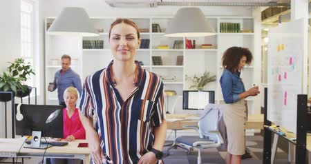 armen over elkaar : Portrait of a happy Caucasian businesswoman working in a busy office, standing with arms crossed smiling to camera with her colleagues working in the background Stockvideo