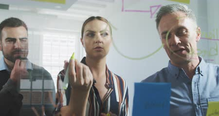 businesspeople : Front view of Caucasian businesswoman and businessmen working in a modern office together, standing by a clear board brainstorming discussing and writing in slow motion Stock Footage