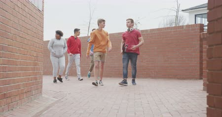 recess : Front view of a multi-ethnic group of teenage male and female school pupils with schoolbags hanging out, walking and talking in their high school grounds on a sunny day, in slow motion