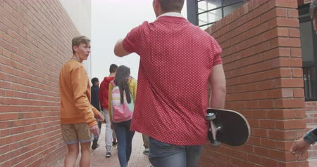 schoolyard : Rear view of a multi-ethnic group of teenage male and female school pupils with schoolbags hanging out, walking and talking in their high school grounds, in slow motion
