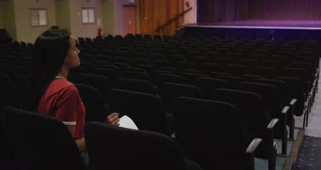 acteur : Side view of a Caucasian teenage girl in an empty high school theater, sitting in the auditorium preparing for a performance, holding a script and learning lines