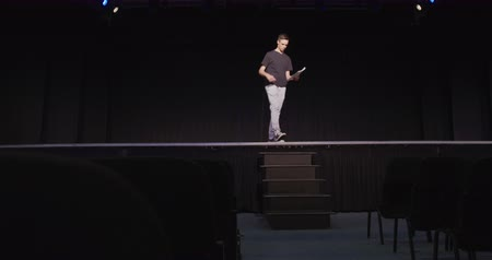acteur : Front view of a Caucasian teenage boy in an high school empty school theater preparing before a performance, sitting on the edge of the stage, holding a script and learning lines Stockvideo