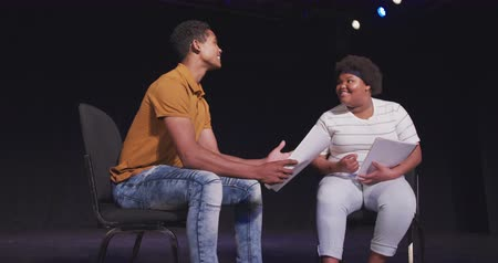 старшей школе : Front view of a mixed race high school teenage boy and African American teenage girl sitting on chairs in an empty school theater preparing before a performance, holding scripts and rehearsing together, in slow motion Стоковые видеозаписи