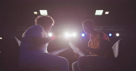 rehearsing : Side view of a high school mixed race teenage boy and African American teenage girl sitting on chairs in an empty school theatre preparing before a performance, holding scripts and rehearsing together, backlit by stage lights, in slow motion Stock Footage