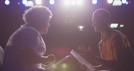 acteur : Side view close up of a mixed race high school teenage boy and African American teenage girl sitting on chairs in an empty school theatre preparing before a performance, holding scripts and rehearsing together, and high fiving, backlit by stage lights, in